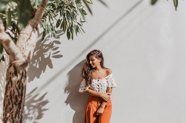 Giovane donna in pantaloni arancioni e camicetta con le spalle nude sorride dolcemente, appoggiandosi al muro bianco sotto l'albero Foto Gratuite
