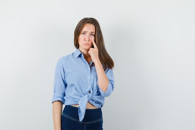 Giovane signora che indica alla palpebra inferiore dell'occhio in camicia blu, pantaloni e che sembra depressa Foto Gratuite