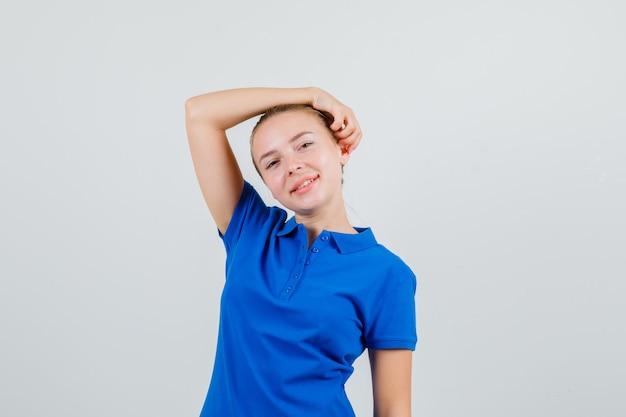 Giovane signora che posa con il braccio alzato sulla testa in maglietta blu e sembra allegra Foto Gratuite