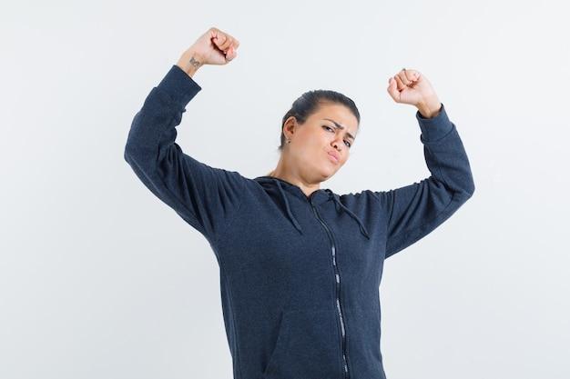재킷에 우승자 제스처를 보여주는 팔을 제기하고 유연하게 보이는 젊은 아가씨. 전면보기. 무료 사진
