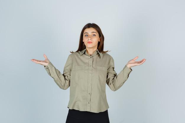 Giovane donna in camicia, gonna che mostra gesto impotente e guardando concentrato Foto Gratuite