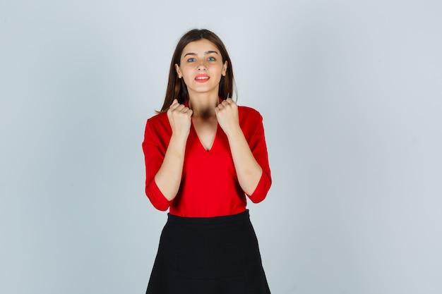 Giovane signora che mostra i pugni chiusi in camicetta rossa, gonna e che sembra allegra Foto Gratuite