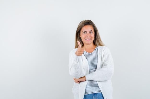 Giovane signora che mostra il pollice in su in maglietta, giacca e sembra felice. vista frontale. Foto Gratuite