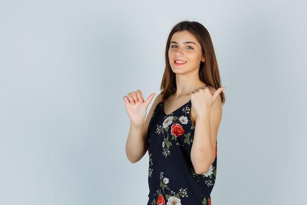 꽃 상단에 엄지 손가락을 표시 하 고 기쁘게 찾고 젊은 아가씨 무료 사진