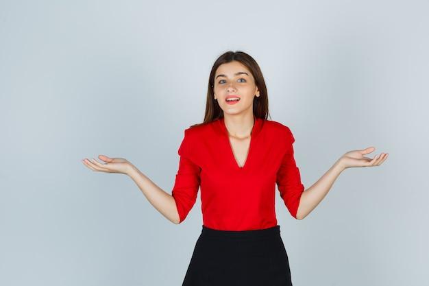 Giovane donna che allarga le palme da parte in camicetta rossa, gonna e sembra allegra Foto Gratuite