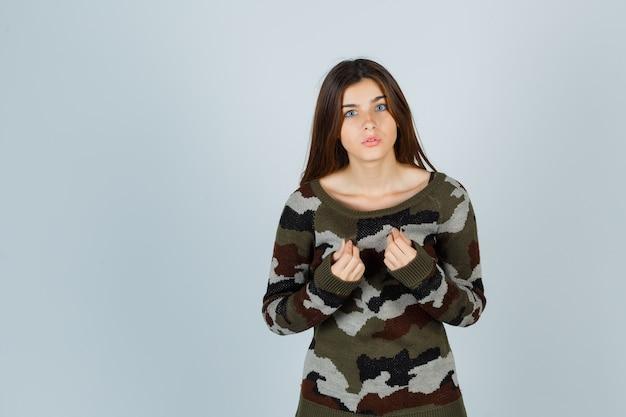 Giovane donna in maglione tenendo le mani vicino al petto e guardando concentrato Foto Gratuite