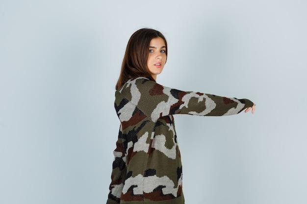 Giovane donna in maglione in posa mentre si gratta la mano e sembra fresca Foto Gratuite