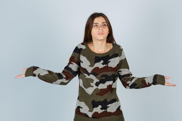 Giovane donna in maglione allargando le palme da parte e guardando concentrato Foto Gratuite