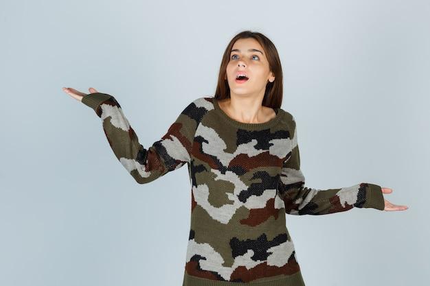Giovane donna in maglione allargando le palme da parte e guardando perplessa Foto Gratuite