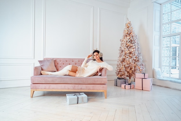 Young lady in white dress on the sofa in christmas time Free Photo