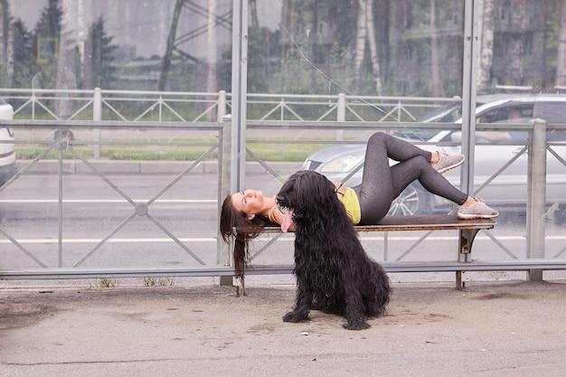 그녀 근처에 검은 Briard와 젊은 아가씨는 버스를 기다리는 동안 대중 교통 역의 벤치에 누워 있습니다. 프리미엄 사진