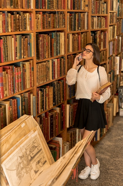 Young lady with glasses talking on phone and holding book Free Photo