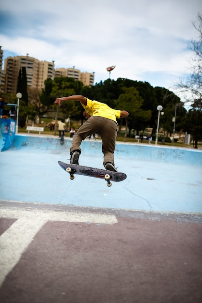 Young latin boy doing stunts with his skate in a skate park. Premium Photo
