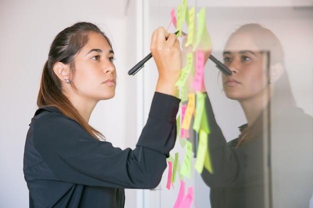 Giovane imprenditrice latina scrivendo su adesivo con pennarello. responsabile femminile bello brunetta sicuro concentrato che condivide l'idea per il progetto e che prende nota. brainstorming, business e concetto di formazione Foto Gratuite