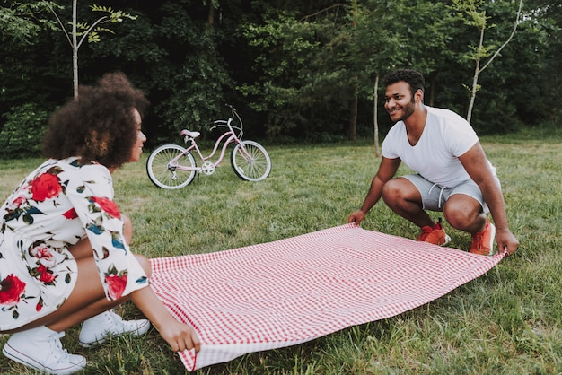 Young latin couple lay tablecloth for picnic Premium Photo