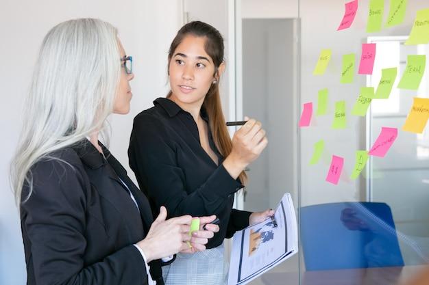 ペンと統計文書を保持し、上司を見て若いラテン系雇用主。自信を持って白髪の女性マネージャーを訓練する同僚に焦点を当てた 無料写真