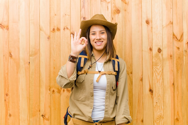 Young latin explorer woman against wooden wall wall Premium Photo