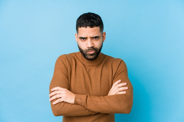 Young latin man against a blue  wall isolated frowning face in displeasure, keeps arms folded. Premium Photo