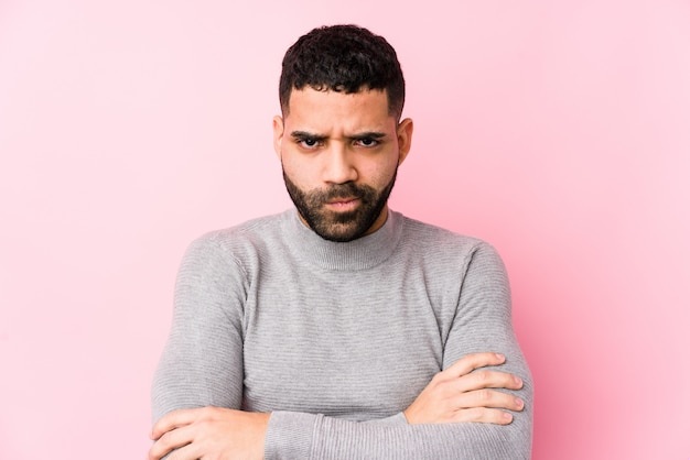 Young latin man against a pink wall isolated frowning face in displeasure, keeps arms folded. Premium Photo