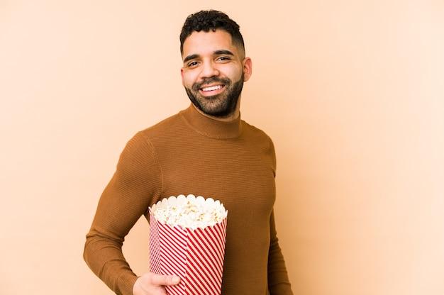 Молодой латинский мужчина, держащий ведро попкорна, смотрит в сторону Premium Фотографии