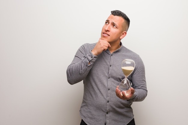 Young latin man holding a sand timer relaxed thinking about something looking at a copy space Premium Photo