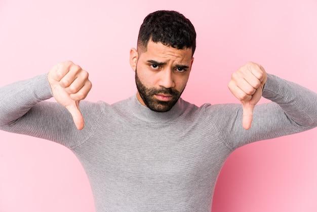 Молодой латинский человек на розовом изолированном, показывая большой палец вниз и выражая неприязнь. Premium Фотографии