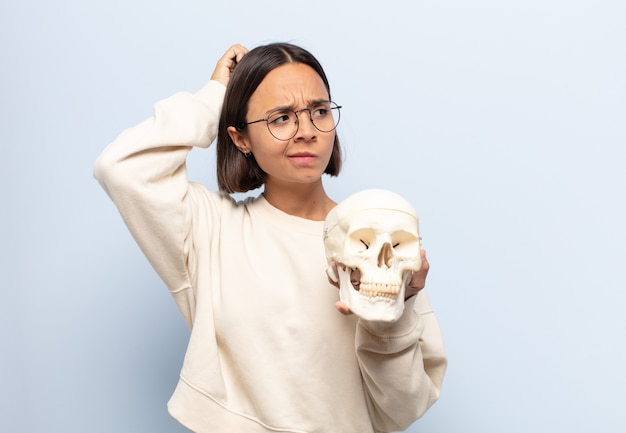 Young latin woman feeling puzzled and confused, scratching head and looking to the side Premium Photo
