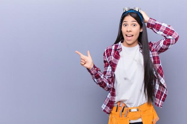 横向きのコピースペースを指す素晴らしいアイデアを実現する、笑って、幸せそうに見えて、前向きで、驚いて若いラテン女性 Premium写真