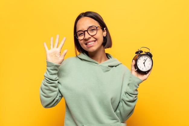 笑顔でフレンドリーに見える若いラテン女性、前に手を前に5または5番を示し、カウントダウン Premium写真