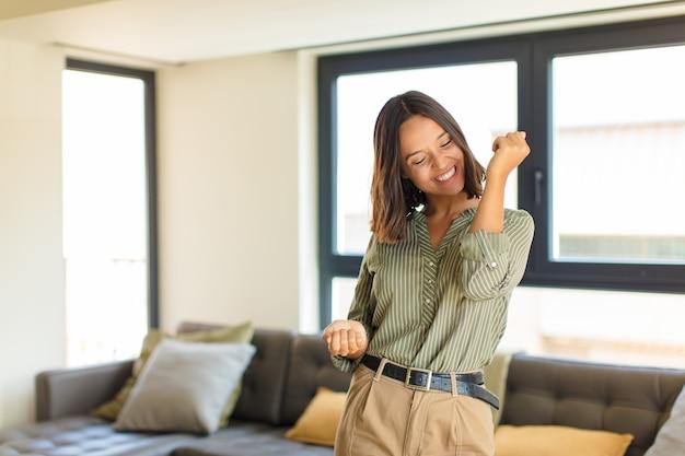 Молодая латинская женщина улыбается, чувствует себя беззаботной, расслабленной и счастливой, танцует и слушает музыку, веселится на вечеринке Premium Фотографии