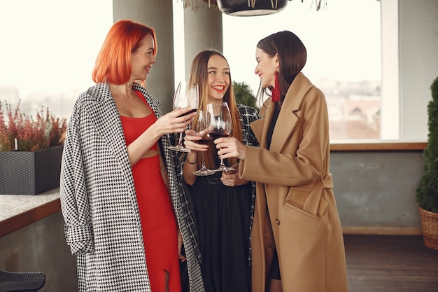 Молодые смеющиеся друзья пьют розовое вино из стекла на улице Бесплатные Фотографии