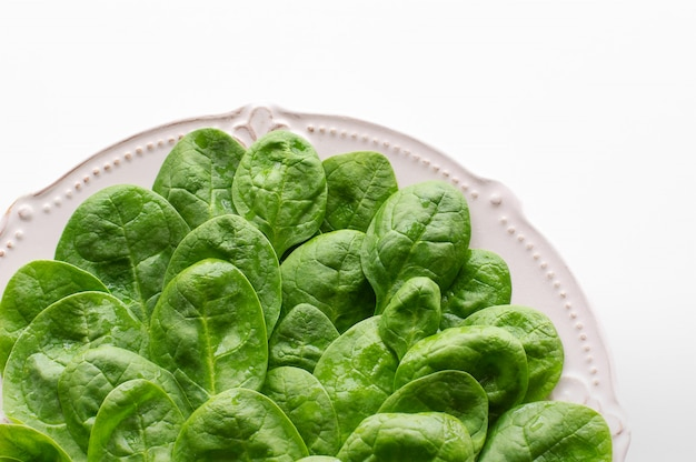 Young leaves of spinach on a plate. Premium Photo