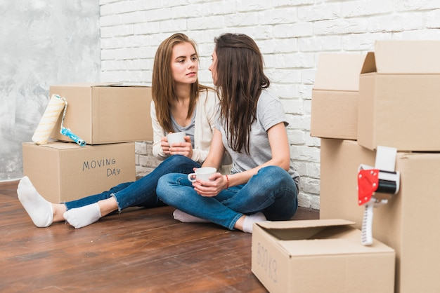 Young lesbian couple holding coffee cup in hands looking at each other sitting among the cardboard boxes Free Photo