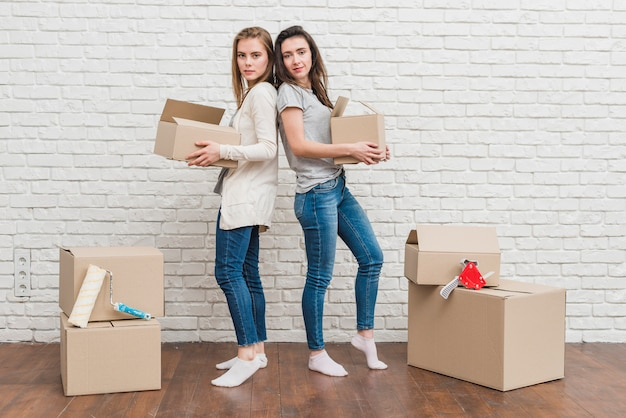 Young lesbian couple holding moving cardboard boxes in hand standing back to back against white wall Free Photo