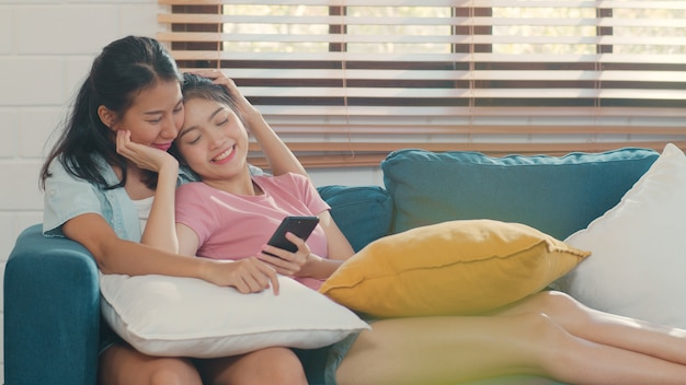 Young lesbian lgbtq women couple using mobile phone at home. Free Photo