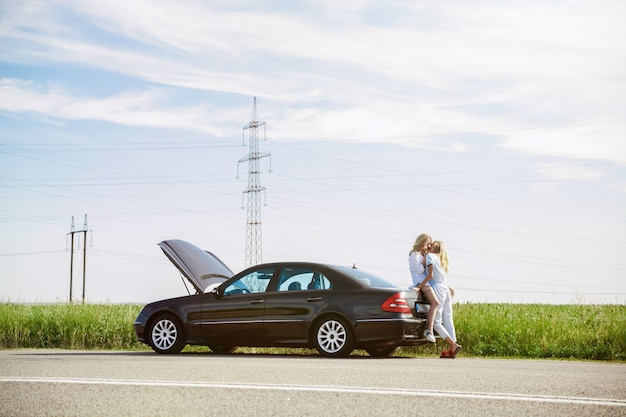 The young lesbian's couple broke down the car while traveling on the way to rest. kissing and cuddling on the car's trunk. relationship, troubles on the road, vacation, holidays, honeymoon concept. Free Photo