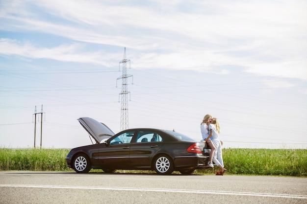 La coppia della giovane lesbica ha rotto la macchina mentre era in viaggio per riposarsi. baci e coccole sul bagagliaio dell'auto. relazione, guai sulla strada, vacanze, vacanze, concetto di luna di miele. Foto Gratuite
