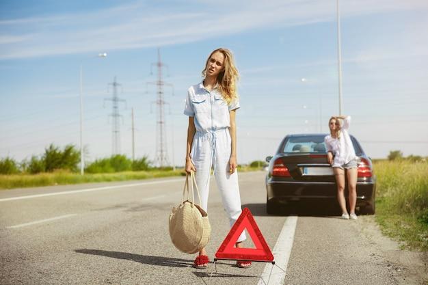 La coppia di giovani lesbiche va in vacanza in macchina in una giornata di sole Foto Gratuite