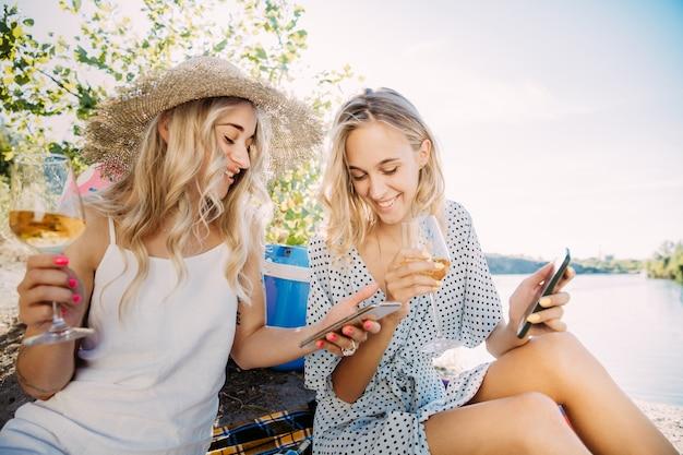 晴れた日に川沿いで楽しんでいる若いレズビアンのカップル。一緒に自然に時間を過ごす女性たち。ワインを飲み、自分撮りをします。関係、愛、夏、週末、新婚旅行の概念。 無料写真