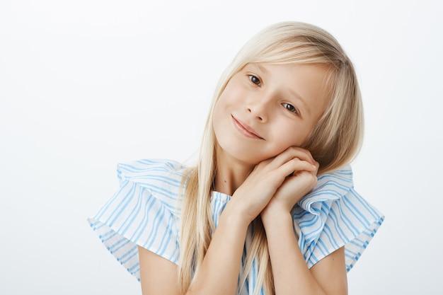 欲しいものを得るために愛らしい顔を作る若い女の子。ブロンドの髪の若い子の思いやりのある、広く笑って、肩に寄りかかって、天使の表情と笑顔で顔の近くで手をつないで 無料写真