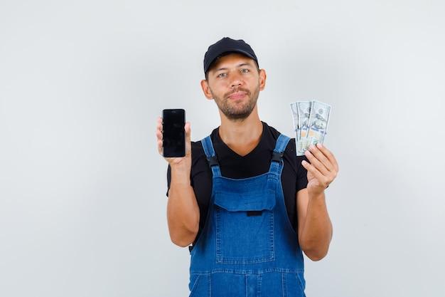Молодой погрузчик держит смартфон и долларовые купюры в форме и выглядит веселым. передний план. Бесплатные Фотографии