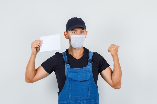 제복을 입은 젊은 로더, 다시, 정면을 가리키는 동안 종이 시트를 들고 마스크. 무료 사진