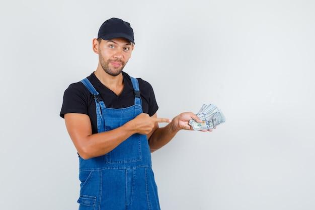 Молодой погрузчик в униформе, указывая на долларовые купюры и глядя веселый, вид спереди. Бесплатные Фотографии