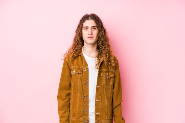 Молодой человек с длинными волосами, позирует, изолированные, счастливые, улыбающиеся и веселые. Premium Фотографии