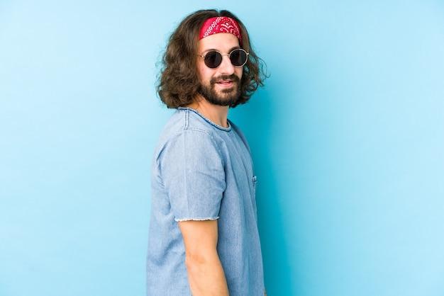 Молодой человек с длинными волосами, одетый в фестивальный хипстерский вид, изолированно выглядит улыбающимся, веселым и приятным. Premium Фотографии