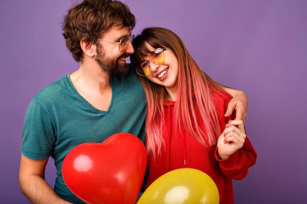 紫の壁、明るいトレンディなカジュアルな服とメガネでポーズをとる愛らしい流行に敏感な若いカップル、抱擁と笑顔、友情と関係の目標、気球を持っている、お祝いの準備ができています。 無料写真