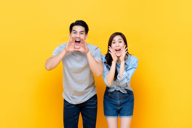 Young lovely asian couple yelling with hands cup around mouths Premium Photo
