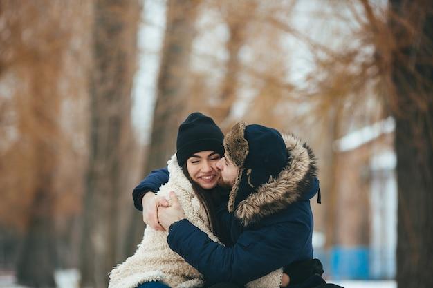Coppia giovane e adorabile che abbraccia nel parco invernale Foto Gratuite