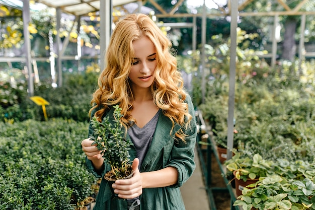 植物の若い恋人は植物園を歩きます。かわいいブロンドの女の子は興味を持って植物を見ます。 無料写真