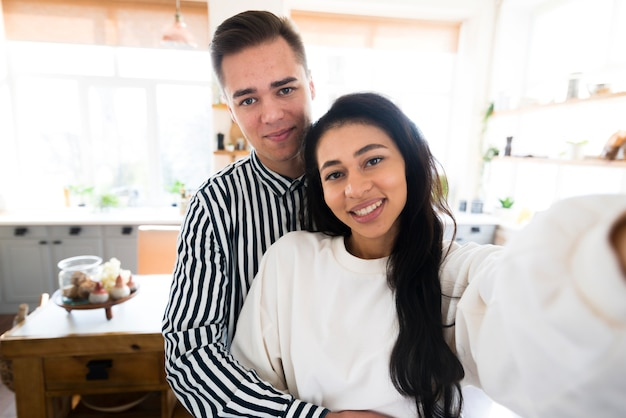 Young lovers hugging and taking selfie in kitchen Free Photo